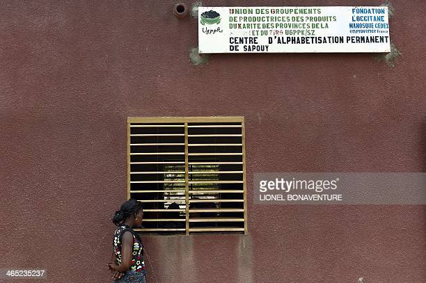 A woman stands outside a literacy center in Leo southcentral Burkina Faso on January 24 2014 French cosmetics company L'Occitane has been working...