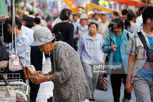 A woman stands outside a store in the Sugamo district of Tokyo Japan on Sunday May 24 2015 Japan's Topix index fell for the first time in nine days...