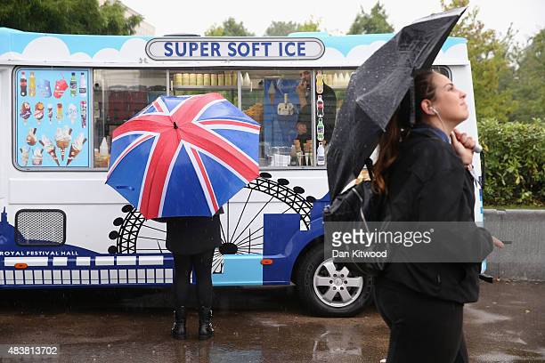 A woman stands outside an ice cream van on the South Bank in heavy rain on August 13 2015 in London England The Met Office has issued an amber...
