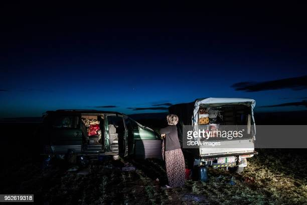A woman stands outside her familys cars now their home in a field in the town of Ahras An estimated 400000 refugees fleeing the twomonthold Turkish...