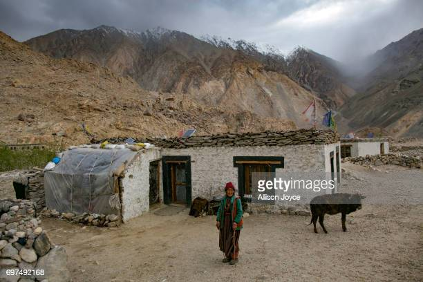 A woman stands outside her house which is powered by solar energy in Tangtse village on June 13 2017 in Ladakh India The cold desert of Ladakh has...