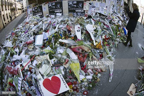 A woman stands outside the headquarters of French satirical weekly Charlie Hebdo in Paris on February 7 next to flowers layed in memory of victims...