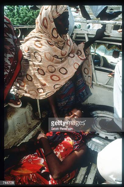 A woman stands over a wounded girl in the back of a pickup truck December 6 1993 in Mogadishu Somalia US gunships attacked the compound of warlord...