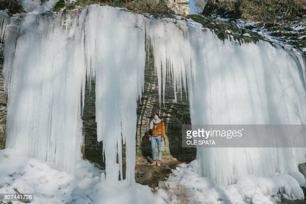 TOPSHOT A woman stands under a frozen waterfall on March 4 2018 in Langenfeld southern Germany / Germany OUT