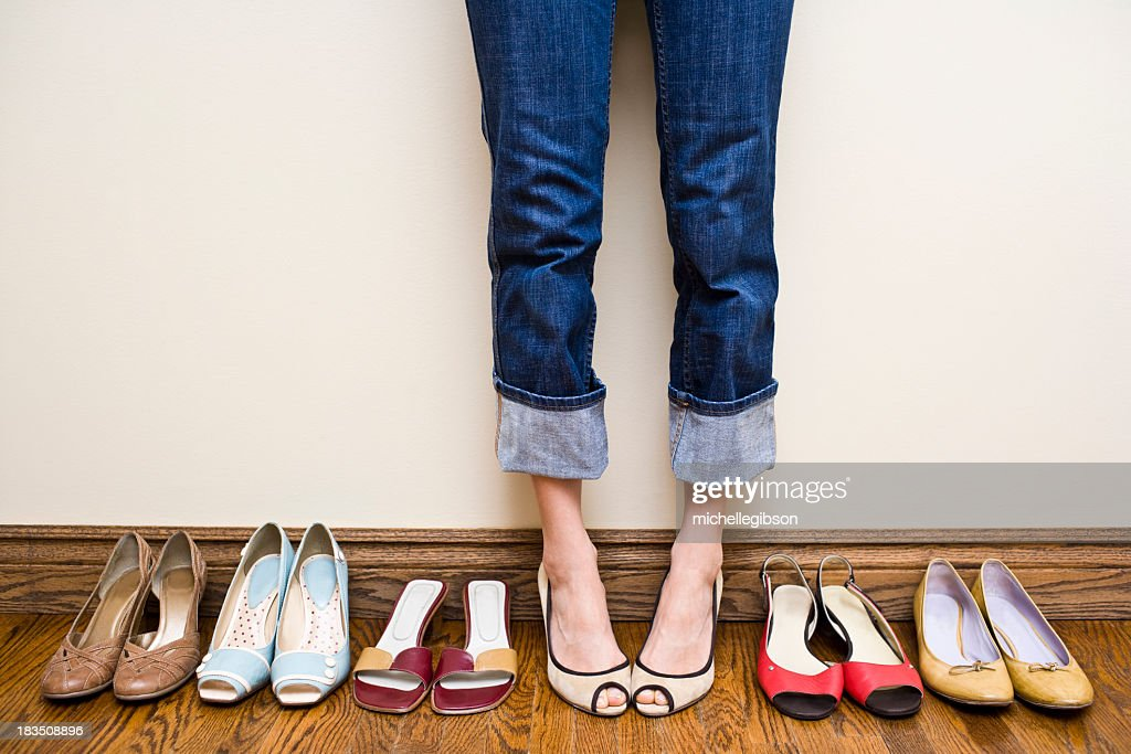 Woman stands wearing heels with her collection of Shoes : Stock Photo
