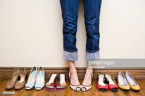woman stands wearing heels with her collection of shoes - nette schoen stockfoto's en -beelden