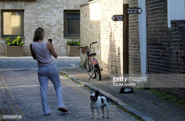 A woman stands with a dog as she photographs a mock signpost giving directions to Barnard Castle southwest of Durham placed near to the home of 10...