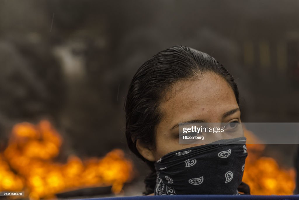 A woman stands with a mask as tires burn during protests against the presidential election of Juan Orlando Hernandez in Tegucigalpa, Honduras, on Monday, Dec. 18, 2017. Honduran electoral authorities declared incumbent Hernandez the winner of the Nov. 26 presidential vote after three weeks in which the nation slid into chaos as ballots were counted and recounted. Photographer: Juan Carlos/Bloomberg via Getty Images