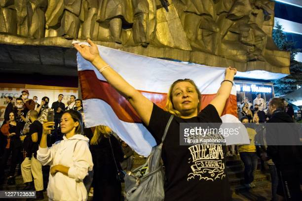 Woman stands with a white-red-white flag as peaceful protestors gather after Belarus registers five out of seven candidates for the presidential...