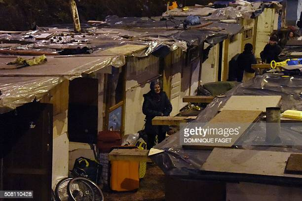 A woman stands with her belongings by makeshift shacks during the evacuation by Gendarmes of a Roma migrants' camp deemed insecure and unsanitary on...