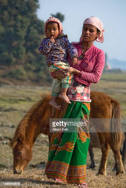 Woman stands with her child in the fields of her farm land in rural Pokhara