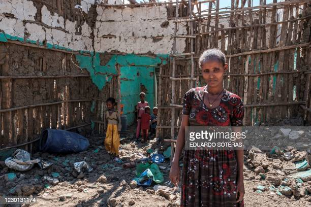 Woman stands with her children amidst the rubbles of her house that was damaged during the fightings that broke out in Ethiopia's Tigray region, in...