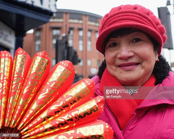 A woman stands with her fan as the Chinese community come together to welcome in the Chinese New Year on February 22 2015 in Newcastle upon Tyne...