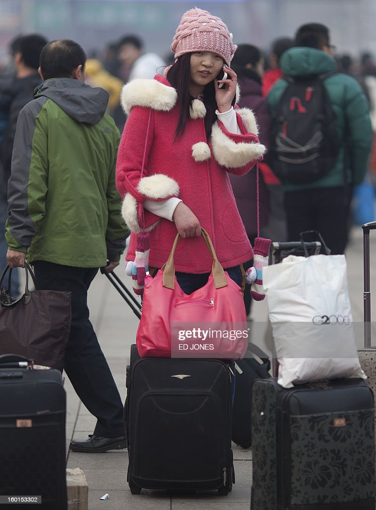 A woman stands with her luggage as she talks on a mobile phone at Beijing Railway Station in Beijing on January 27, 2013. The world's largest annual migration began in China with tens of thousands in the capital boarding trains to journey home for next month's Lunar New Year celebrations. AFP PHOTO / Ed Jones