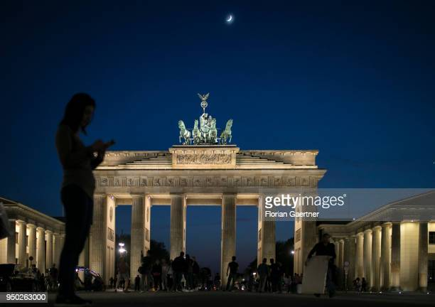 A woman stands with her smartphone in front of the Brandenburg Gate on April 19 2018 in Berlin Deutschland