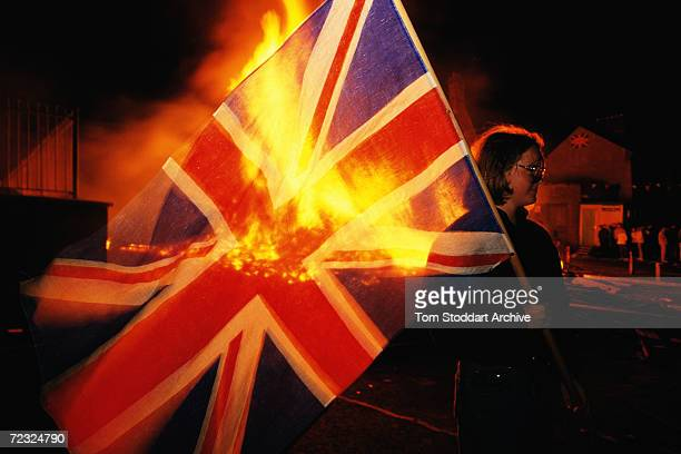 A woman stands witha United Kingdom flag during the sectarian violence that followed the Apprentice boys march