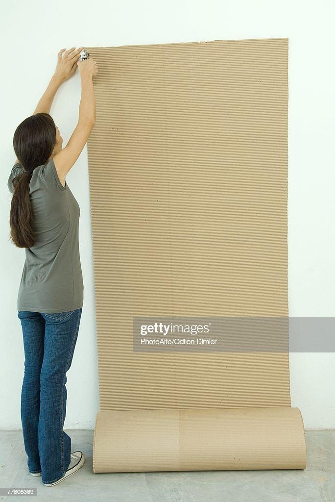 Woman stapling corrugated cardboard to wall : Stock-Foto