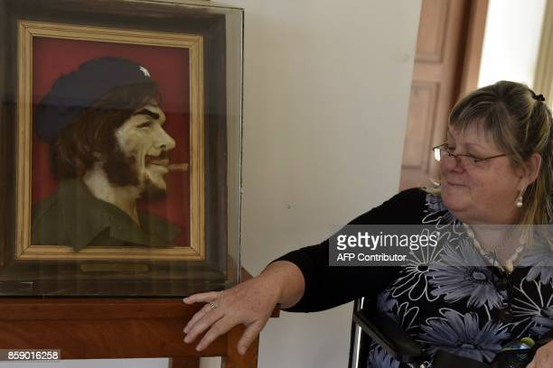 A woman stares at a painting of Argentineborn guerrilla leader Ernesto Che Guevara in Vallegrande Bolivia on October 8 2017 during the 50th...