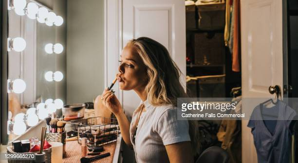 a woman stares into an illuminated mirror as she concentrates while applying lipgloss - backstage stock pictures, royalty-free photos & images
