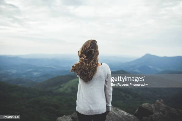 woman stares out at a beautiful mountain scene - design elements stock photos and pictures