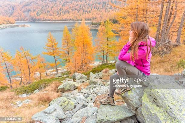 Woman staring at colorful landscape of Lake Devero, Alpe Veglia and Alpe Devero Natural Park, Baceno, Verbano Cusio Ossola province, Piedmont, Italy