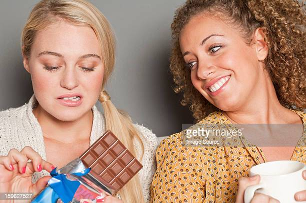Woman staring at friend holding chocolate