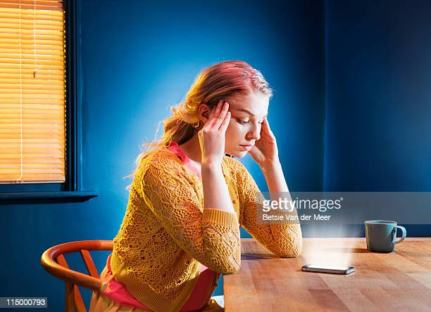 woman staring at mobilephone. - anxiety stock pictures, royalty-free photos & images