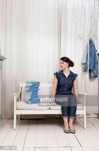 Woman staring at stack of books