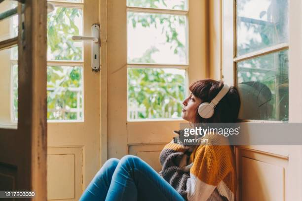 woman staying home due to covid-19 pandemic - listening stock pictures, royalty-free photos & images