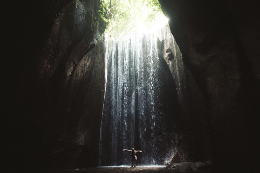 Woman staying under hidden waterfall in cave on Bali 1082359040