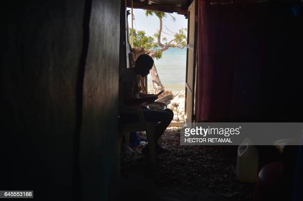 TOPSHOT A woman stays in the interior of a house in the commune of RocheaBateaux southwestern Haiti on February 25 that was affected by the passage...