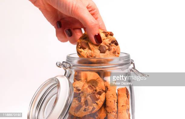 woman stealing a cookie from the cookie jar - caught in the act stock pictures, royalty-free photos & images