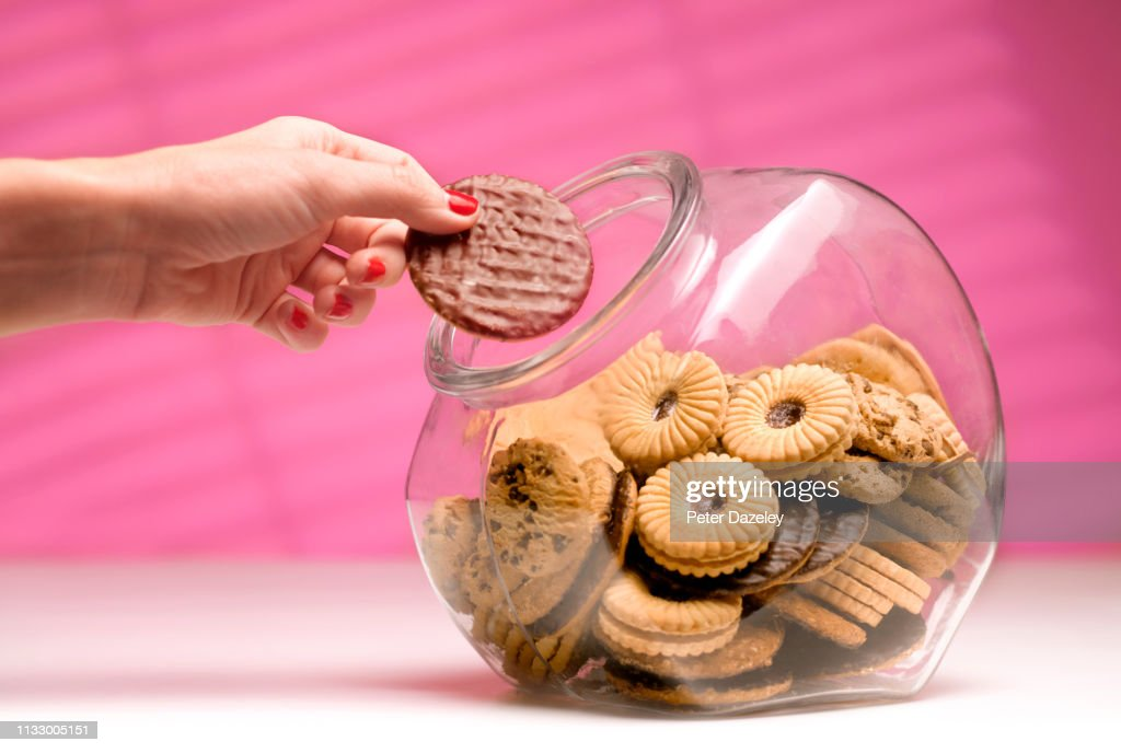 Woman stealing biscuit, caught in the act. : Stock Photo