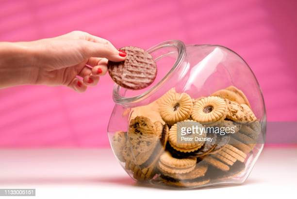 woman stealing biscuit, caught in the act. - one woman only stock pictures, royalty-free photos & images