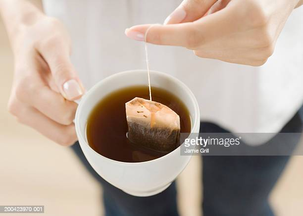 Woman steeping tea bag in cup, close-up, elevated view