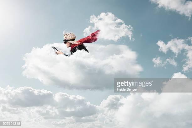 Woman steering in clouds, digital composite
