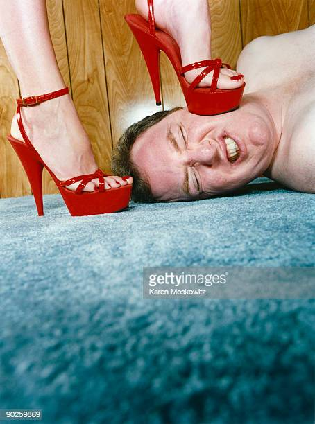woman stepping on man - risque woman stock photos and pictures
