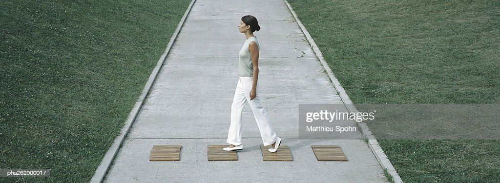 Woman stepping on wood squares across concrete path, full length : Stockfoto