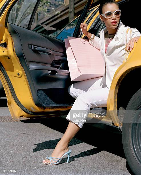 A woman stepping out of a taxi with shopping bags, New York City, USA