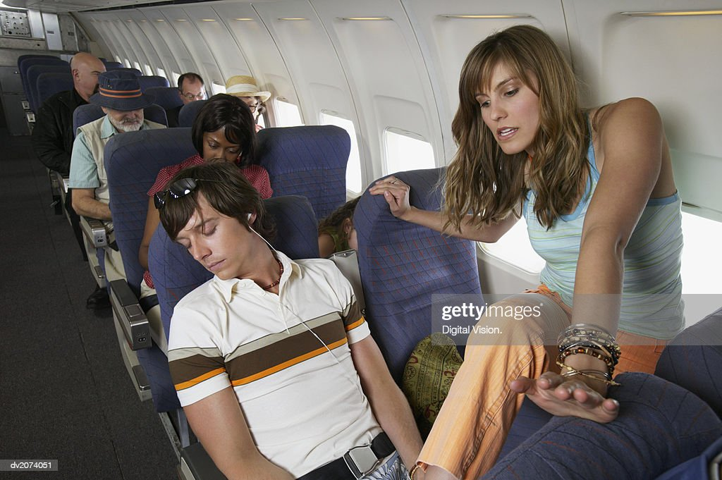 Woman Stepping Over a Man Sleeping in His Seat on a Commercial Aeroplane : Stock Photo