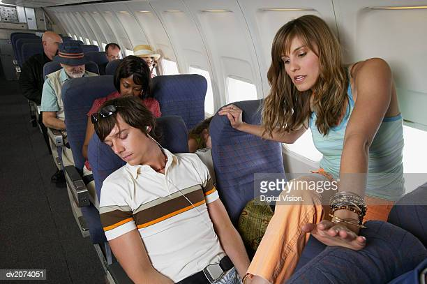 woman stepping over a man sleeping in his seat on a commercial aeroplane - narrow stock pictures, royalty-free photos & images
