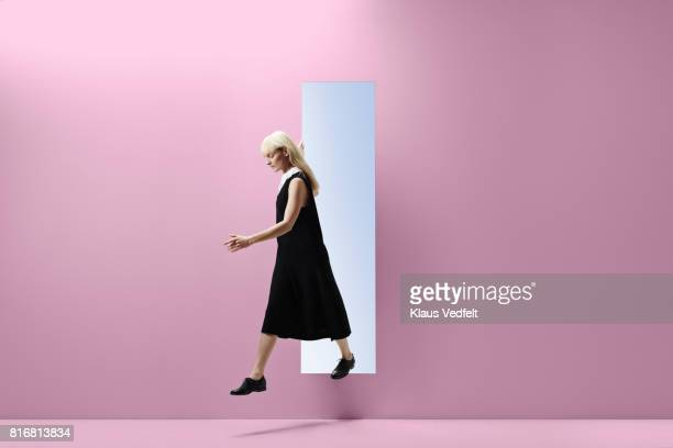 woman stepping threw rectangular opening of coloured wall - bleached hair stock photos and pictures