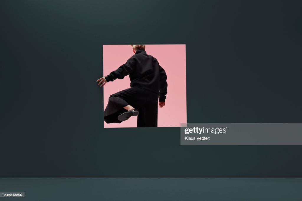 Woman stepping threw square opening in coloured wall : Stock Photo
