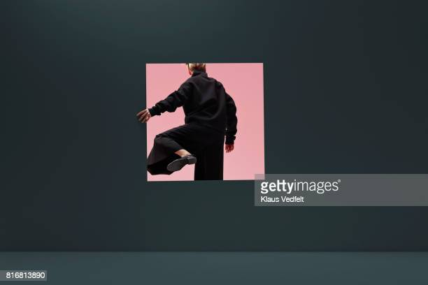 woman stepping threw square opening in coloured wall - verandering stockfoto's en -beelden