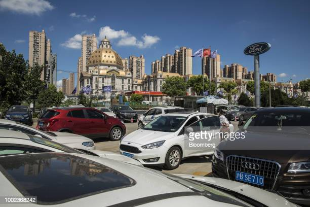 A woman steps inside a Ford Motor Co vehicle at a Ford dealership in Shanghai China on Thursday July 19 2018 The fledgling USChina trade war will...