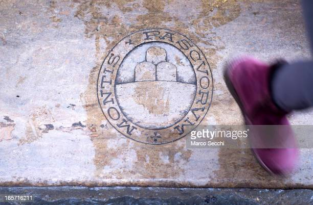 A woman steps on a Banca Monte Paschi paving stone whilst leaving a branch in the city centre on April 5 2013 in Siena Italy The Bank of Italy has...