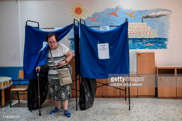 Woman steps out of a polling booth during Greek general elections in Athens on July 7, 2019. - Greek voters are casting their ballots in the...