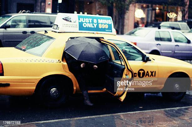 CONTENT] A woman steps out of a taxi during a rainy afternoon in the Meat Packing District of New York City