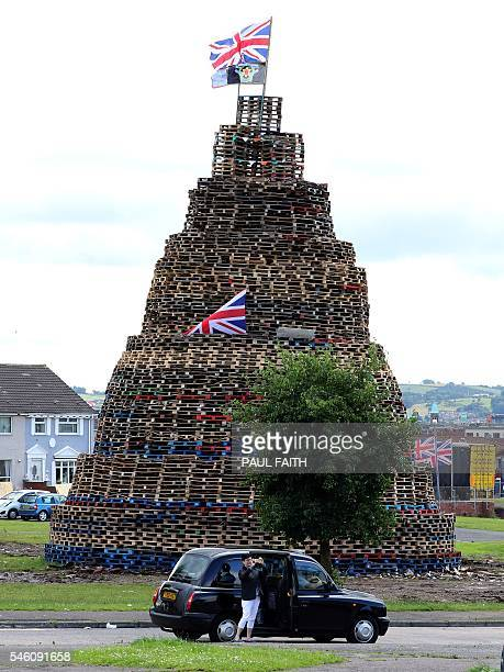 A woman steps out of a taxi to take a photograph of one of the largest 11th night Bonfires in the lower Shankill road area of Belfast Northern...