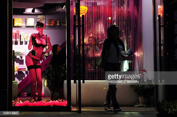 A woman steps out of the Boutique De L'Amour sex shop in Beijing on June 13 2009 Stores selling sex paraphernalia are on seemingly every block in...